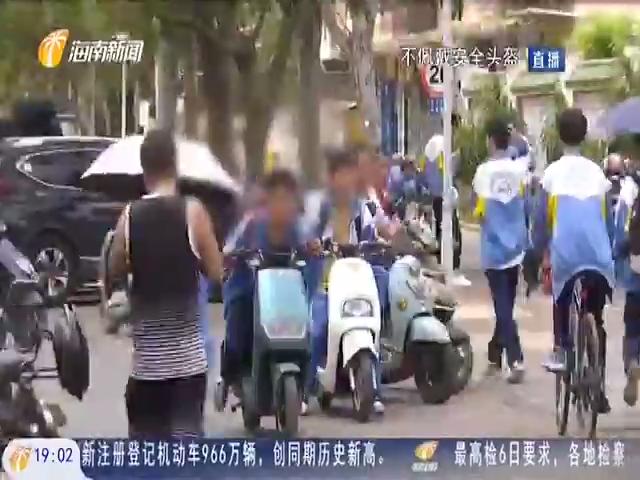 临高:不戴安全头盔打伞骑车 校门口安全隐患令人忧