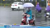 雨天骑车打伞隐患多 穿雨衣避开积水路段