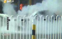 轿车当街突然起火 众人合力将其扑灭