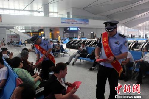 资料图: 青岛铁路公安处民警向旅客发放安全宣传资料。 梁西征 摄
