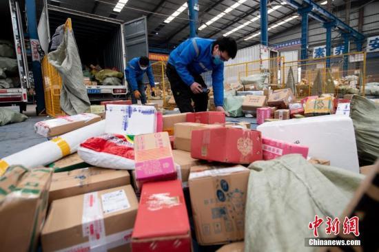 资料图:快递公司员工戴着口罩分拣包裹。<a target='_blank' href='http://www.chinanews.com/'>中新社</a>记者 韦亮 摄