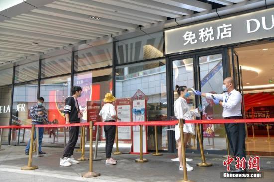资料图:民众佩戴口罩在海口日月广场免税店选购免税商品。骆云飞 摄