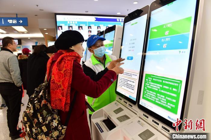 资料图:患者在指导下使用人脸识别系统预约专家号。 王广兆 摄